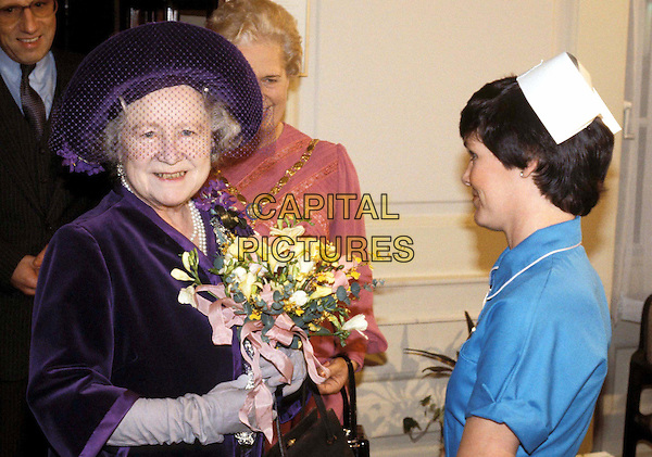HM THE QUEEN MOTHER..1982.. half length, half-length, flowers, purple hat, royalty, dead, deceased..www.capitalpictures.com..sales@capitalpictures.com..©Capital Pictures