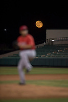 A harvest moon rises behind AZL Angels relief pitcher Kiber Arvelaez (31) as he delivers a pitch during an Arizona League game against the AZL Indians 2 at Tempe Diablo Stadium on June 30, 2018 in Tempe, Arizona. The AZL Indians 2 defeated the AZL Angels by a score of 13-8. (Zachary Lucy/Four Seam Images)