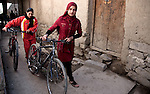 4 APRIL 2012, Kabul, Afghanistan:  Arzoo Omid (21 right) and Mariam Mohammadi (24) lead their bikes through the narrow Kabul lanes near their home. The girls are training to become the vanguard of Afghan competitive womens cycling. They get a miserable allowance from the Government as they are not considered viable prospects for success in the sport. They also meet with plenty of resistance from conservative society but train and compete against the odds often riding in a peleton of men to mask their gender. Picture by Graham Crouch/The Australian