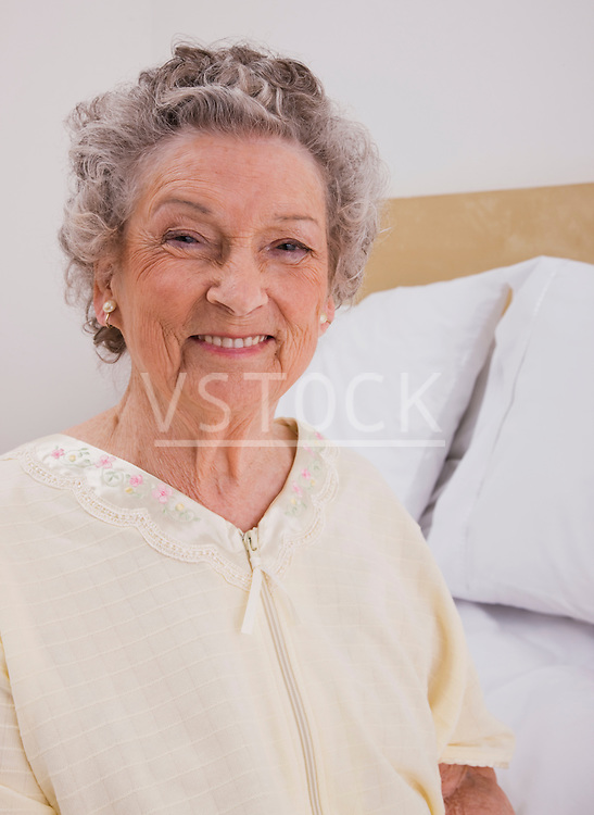 Portrait of smiling senior woman sitting on bed