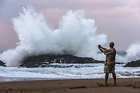 At twilight, a man takes a photo of a massive wave exploding onto the rocky shore at Lumahai Beach on Kaua'i.
