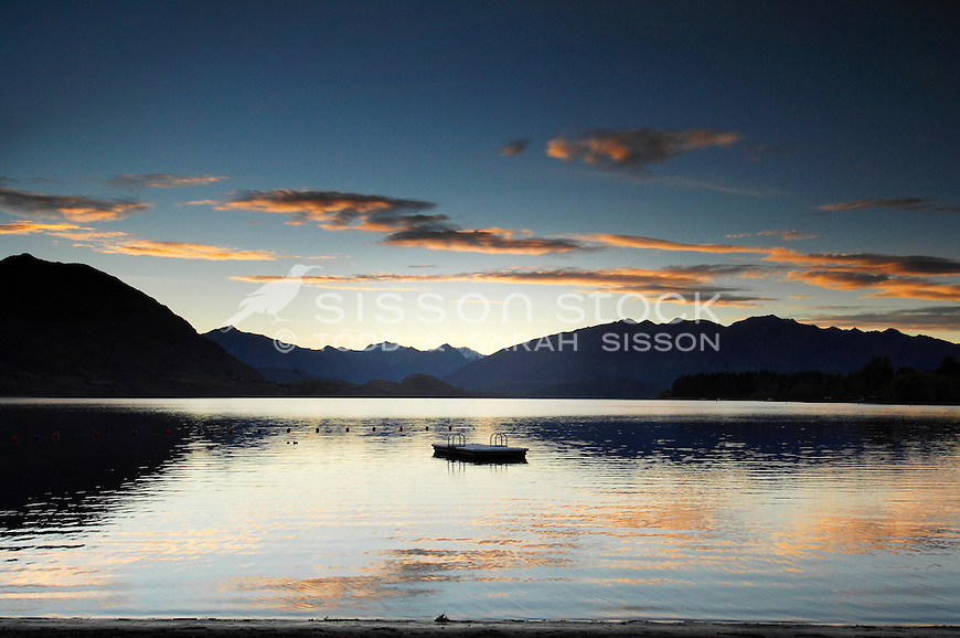 New Zealand Sunset Picutre | Mountains and pontoon silhouetted at sunset, Lake Wanaka, South Island, New Zealand<br /> <br /> SORRY - NO NEW ZEALAND SOUVENIR OR POSTCARD LICENCING PERMITTED