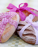 Rustic breads tied with pretty checked ribbons on a green and white checked tablecloth