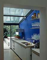 The upbeat bright blue wall breaks up a linear kitchen that features angular fittings and industrial surfaces