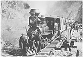 A mostly frontal view of D&amp;RG #25 with a 6-car passenger train halted for passenger exploration on a trestle in a canon.  Three men are posed on the locomotive pilot while the rest are alongside the train.<br /> D&amp;RG    ca. 1895