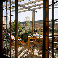 Viewed through open French windows is the green and tranquil roof terrace of this house in Cape Town