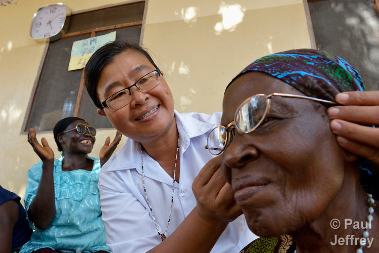 "Sister Joana Mai Hla Kyi, a member from Myanmar of the Sisters of Our Lady of the Missions, helps Katherine Chimoteo, a woman in Riimenze, South Sudan, who says she is ""about 70"", try on eyeglasses so that she can read for the first time in several years. The nun is a member of Solidarity with South Sudan, a pastoral and teaching presence of Catholic priests, sisters and brothers from around the world."