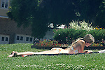 YOUNG WOMAN IN BIKINI SUN BATHS READING BOOK