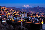 Snowcapped Mount Illimani rises above the illuminated city of La Paz, Bolivia.  The Bridge of the Americas crosses the ravine of Rio Choqueyapu, connecting the neighborhoods of Sopocachi and Miraflores.