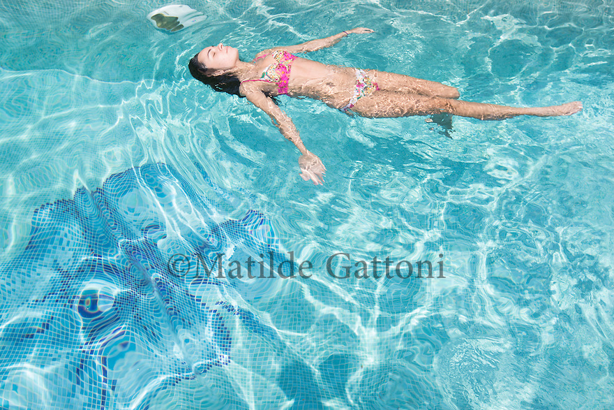"""Romania - Timisoara - Lynette Smith, 20, swimming in the pool at the Live Cams Mansion. Lynette is the newest model in the studio. She has lived in Timisoara for the past two years, splitting her time between camming and studying computer science. """"At the university people talk a lot about camming. Many students do it, because is the easiest way to earn some money"""" she explains. Despite that, Lynette doesn't plan to tell her friends and parents what she does, as part of the Romanian society still equates camming to prostitution.As the youngest girl in the studio, she often speak with her elder and more experienced colleagues. """"I like talking to them and hear about what kind of customers they have"""" she explains. """"A lot of them are married and go online because they don't want to cheat their wives."""""""