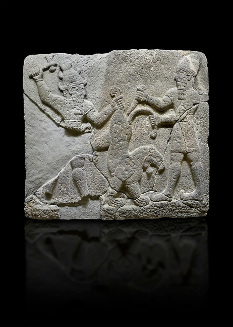 Photo of Hittite relief sculpted orthostat stone panel of Herald's Wall Basalt, Karkamıs, (Kargamıs), Carchemish (Karkemish), 900-700 B.C. Anatolian Civilisations Museum, Ankara, Turkey.<br /> <br /> On the right is a bearded human figure with a short skirt; with the dagger in his right hand, he is stabbing the lion standing on his front legs while holding the lion's tail with his left hand. On the left is a bearded god figure with a horned-headdress, who grasps the lion's hind leg while holding the ax over his head with his right hand. <br /> <br /> Against a black background.