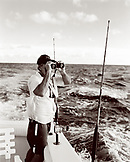 USA, Florida, boat captain looking through binoculars for fish and birds, Islamorada (B&W)