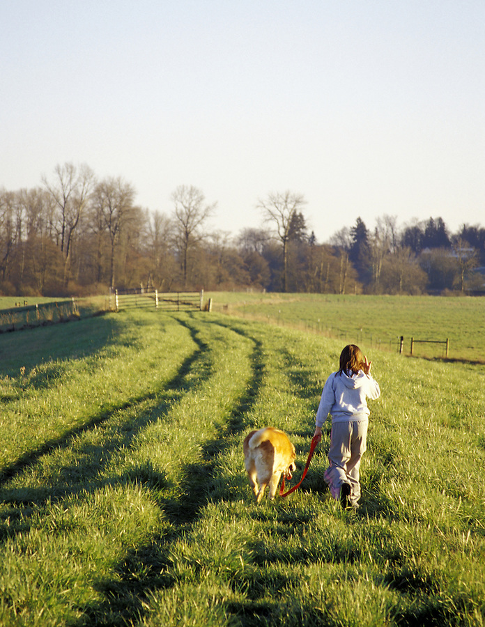 Girl walking dog along Snohomish River dike, Snohomish, Washington