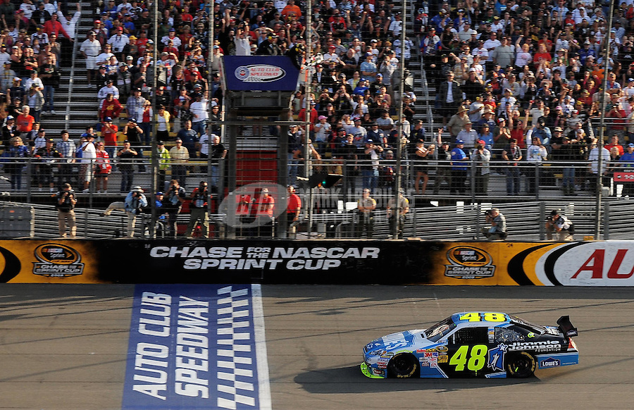 Oct. 11, 2009; Fontana, CA, USA; NASCAR Sprint Cup Series driver Jimmie Johnson takes the checkered flag to win the Pepsi 500 at Auto Club Speedway. Mandatory Credit: Mark J. Rebilas-