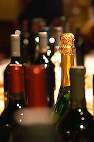 Bottles of wine and sparkling wine on a table for a tasting. The sparkling (champagne) bottle in focus the other bottles out of focus blurred. Montevideo, Uruguay, South America Uruguay wine production institute Instituto Nacional de Vitivinicultura INAVI,