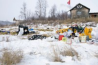 Mitch Seavey feeds dogs as his sled and gear are piled on top of nearly snowless grass at the half-way ghost town of Iditarod