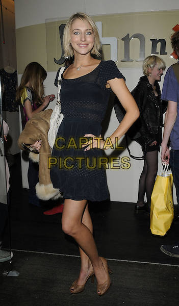 ALI BASTIAN .At the Johnnie B clothing label Launch Party, Oui Rooms, London, England, UK, .April 22nd 2010..full length black dress beige peep toe shoes hand on hip white bag .CAP/CAN.©Can Nguyen/Capital Pictures.