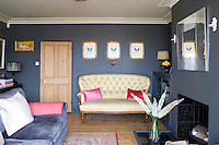 In the living room walls painted in a matt graphite create a stunning backdrop for works of art and furniture
