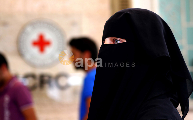 Veiled Palestinian woman walks in front of the red cross headquarters during a rally after a prisoner swap between Hamas and Israel, in Gaza City October 12, 2011. Israelis welcomed on Wednesday a major prisoner swap that will free soldier Gilad Shalit after five years in captivity in return for the release of 1,000 Palestinians, but emotions were mixed over the lopsided exchange negotiated with Hamas. Photo by Ashraf Amra