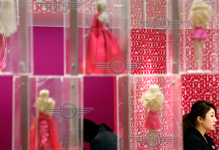 An attendant stands next to a display of dolls during the opening of a flagship Barbie store. The inauguration of the building was timed to coincide with the 50th anniversary of the doll's first ever sale.