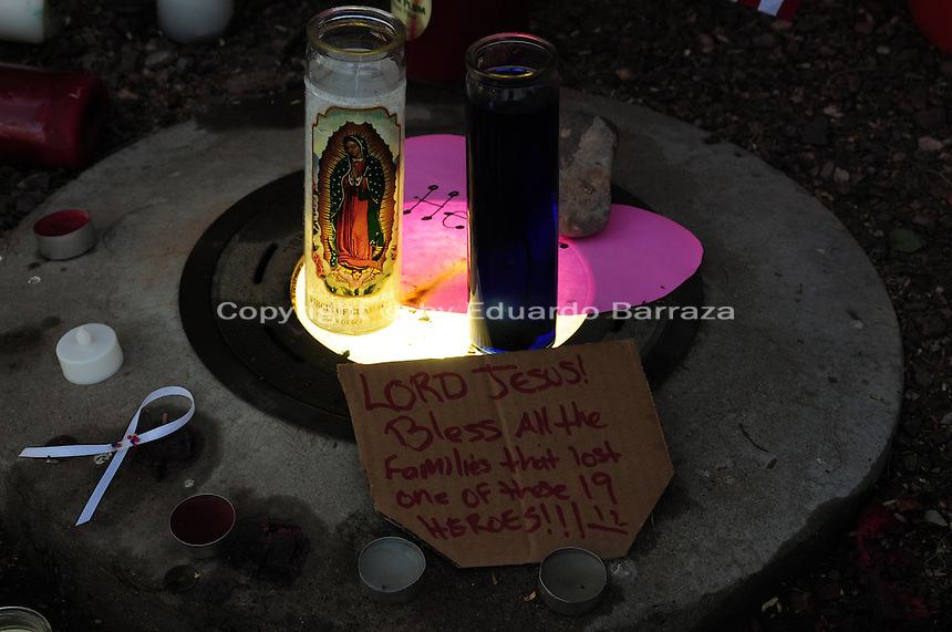Phoenix, Arizona. July 3, 2013. A small makeshift memorial for the 19 Arizona firefighters who died on June 30 battling the Yarnell Hill wildfire was built outside the Forensic Science Center in Phoenix, where autopsies are being conducted. Religious candles were placed in a small memorial made to pay tribute to the 19 men who were not able to escape the Yarnell Hill wildfire in Central Arizona. Photo by Eduardo Barraza © 2013