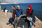 Left to right, Muhannad, Ali, and Ali's daughter Salam, all from Yarmouk Palestinian camp in Syria, wait at the Coast Guard detention camp on Chios Island, Greece, Oct. 5, 2014. Migrants who are found or rescued nearby spend at least a couple of days here before going to the police detention camp.