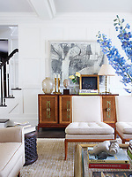 In the living room, the panelled walls are decorated in off-white and neutral tones, the mid-century furnishings include Harvey Probber armchairs in a Brunschwig & Fils fabric, and T.H. Robsjohn-Gibbings slipper chairs; the 1960s cocktail table is by Mastercraft and the rug is from ABC Carpet & Home.