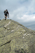 Hiker climbs large boulder on the King Ravine Trail  in the White Mountains, New Hampshire USA