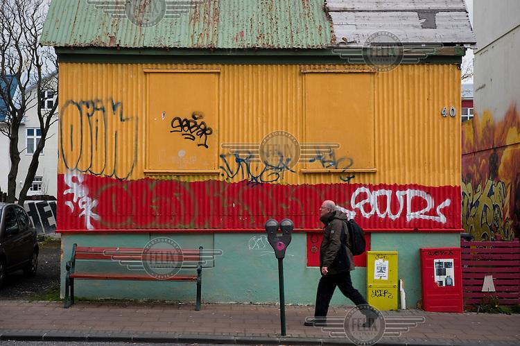 A man walks past a graffiti covered house.