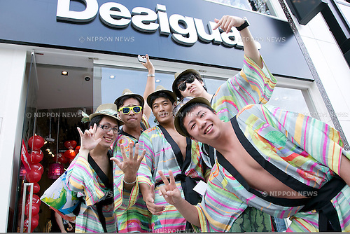 """Tokyo, Japan - Customers pose for cameras outside the Desigual store in Tokyo's Harajuku fashion district. A fashion chain called """"Seminaked Party by Desigual"""" offers the first 100 customers (wearing swimsuit) free clothing items at the grand opening in Tokyo, Japan, June 22, 2013. More than 4,000 people attend the Seminaked Party around the world. (Photo by Rodrigo Reyes Marin/AFLO)"""