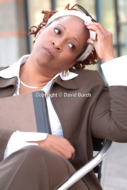 African American woman holding book, thinking