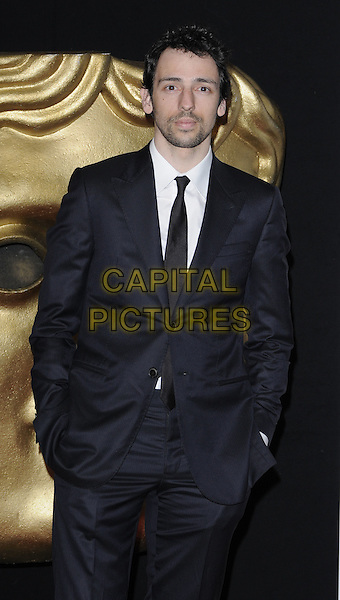 RALF LITTLE .At the British Academy Video Games Awards, London HIlton Hotel, Park Lane, London, England, UK, March 19th 2010..BAFTA half length navy blue tie suit black white shirt hands in pockets facial hair beard .CAP/CAN.©Can Nguyen/Capital Pictures
