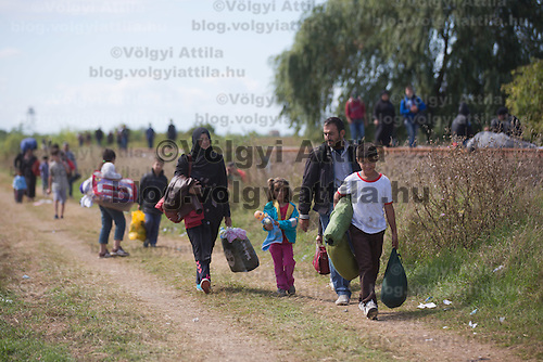 Illegal migrants walk on a dirt road after crossing the border between Hungary and Serbia near Roszke (about 174 km South of capital city Budapest), Hungary on September 07, 2015. ATTILA VOLGYI
