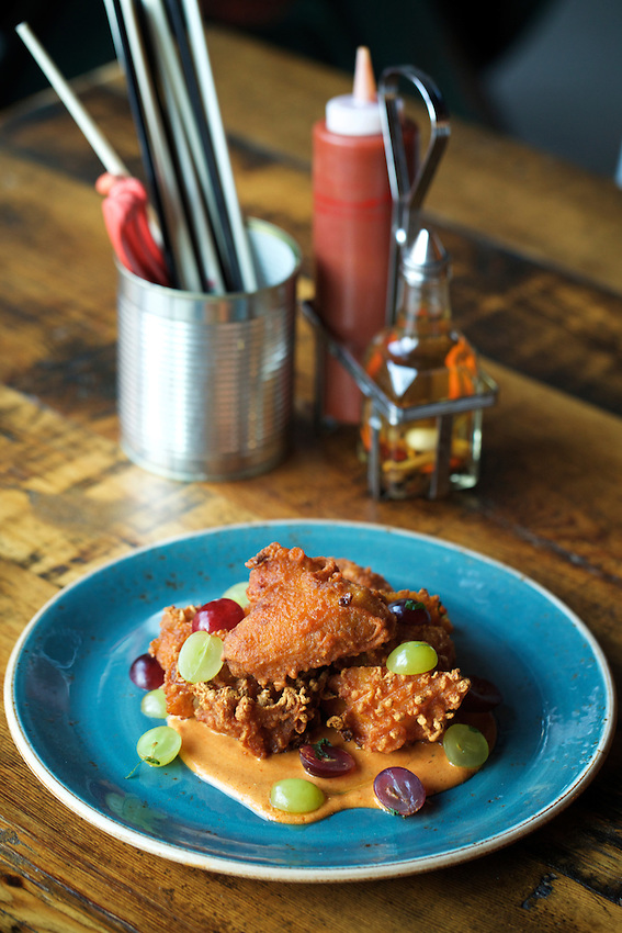 Jersey City, NJ - JANUARY 19, 2016: Korean Fried Chicken with kimchi yogurt and seasonal fruit at Talde on Erie Street, which serves chef Dale Talde's 'inauthentic' Asian-American cuisine.<br /> <br /> CREDIT: Clay Williams for Edible Jersey.<br /> <br /> &copy; Clay Williams / claywilliamsphoto.com
