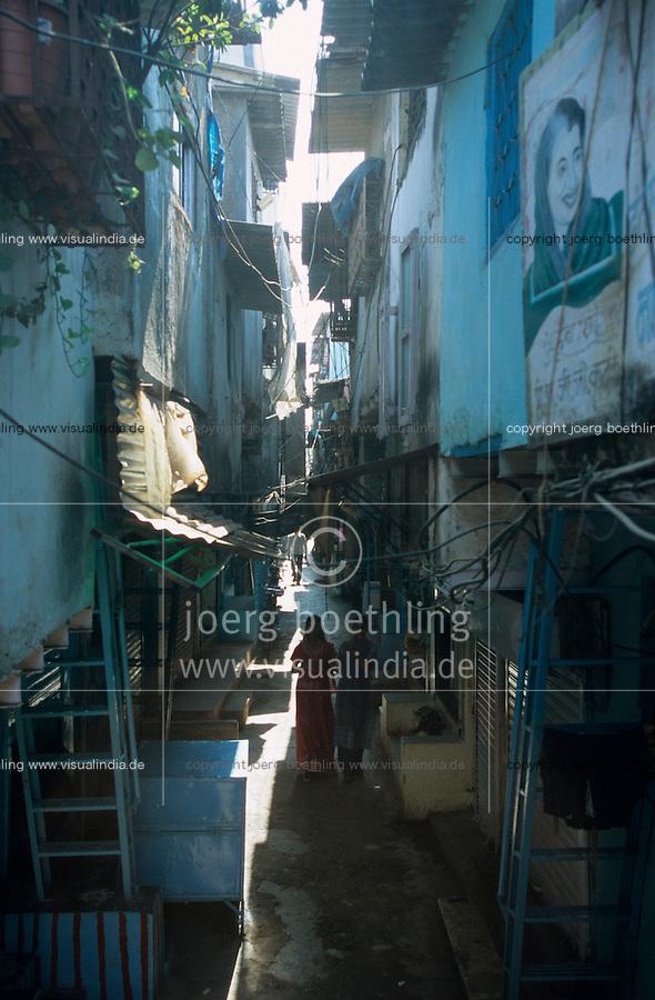 INDIEN Megacity Metropole Mumbai Bombay, Menschen leben in Huetten im Slum Dharavi, enge Gasse / INDIA Mumbai Bombay, Dharavi slum, huts of migrants and picture of Indira Gandhi