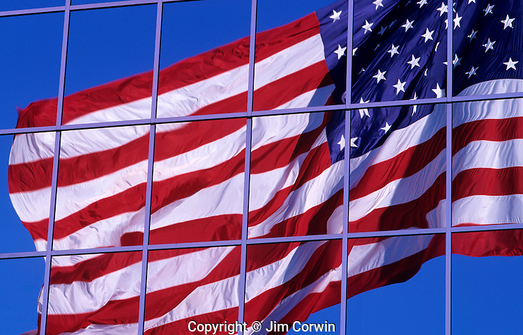 American Flag, Stars and Stripes, waving in the wind with blue sky, sunset light, with flag reflected in corporate building windows