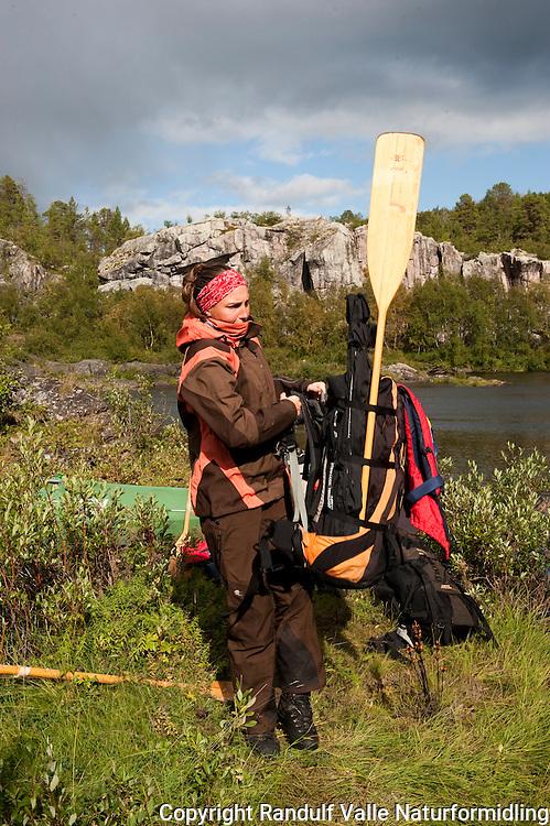 Dame gjør seg klar til å bære forbil Storfossen i Karasjokka. ---- Woman preparing to portage past Storfossen in Karasjokka.