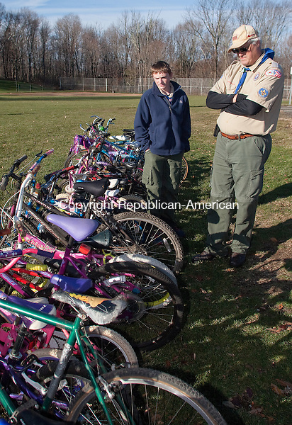 MIDDLEBURY, CT.- 23 NOVEMBER 2013 - 112313JW03 - Boy Scout Troop 283 scout Joe Von Culin looks over a collection of donated bikes with his father Asst. Scout Master Rich Von Culin Saturday afternoon at the Shepardson Community Center. The drive by Von Culin as an Eagle project brought in an estimated donation of over 100 bicycles to the Little Angels Program, which was created in 1980 to help low-income youth and adults obtain bikes for transport and recreation.<br /> Jonathan Wilcox Republican-American