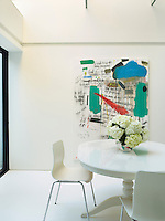 A modern artwork by Norman Hyams dominates the open plan dining area on the lower ground floor which is furnished with a white table and chairs from Ikea