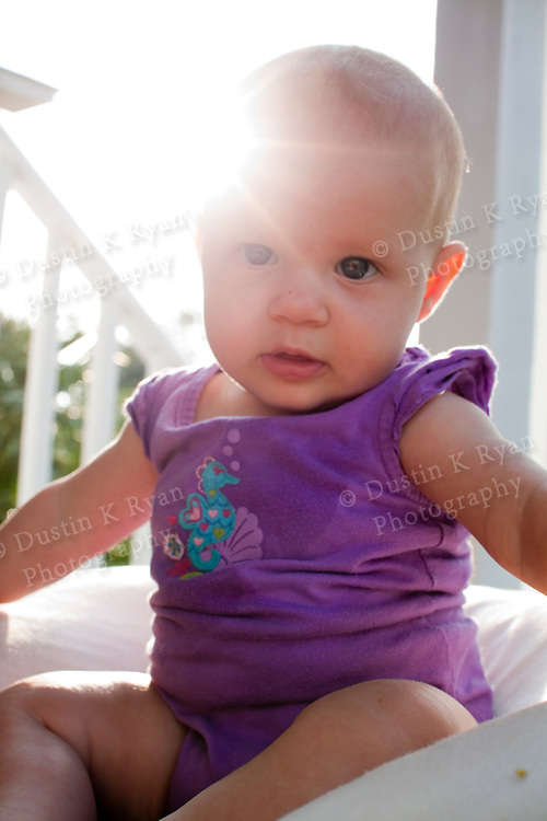 Baby girl 6 months old on the front porch during sunrise blue eyes