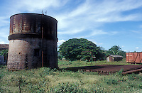 Old brick and metal water tower and pile of railway tracks, Sitio del Nino train station, El Salvador, Central America