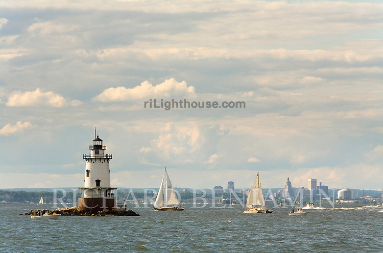 Boats sail past Conimicut Light on a cloudy day.