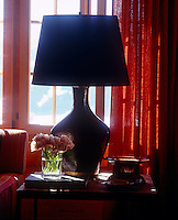 Silhouette of a lamp with a patent leather base in front of a window in the living room