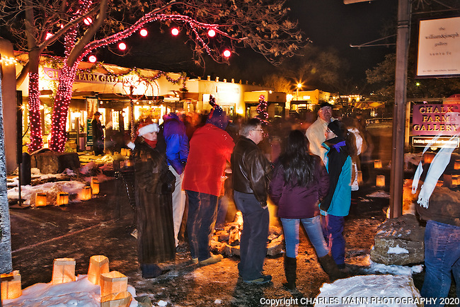 Strollers gather to warm themselves around small fires called luminarias during the annual Christmas Eve celebration on Canyon Road in Santa Fe, New Mexico