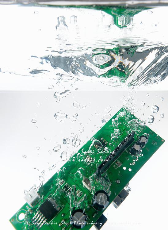 Integrated circuit splashing underwater, white background, studio