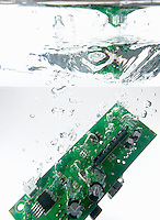 Integrated circuit splashing underwater, white background, studio