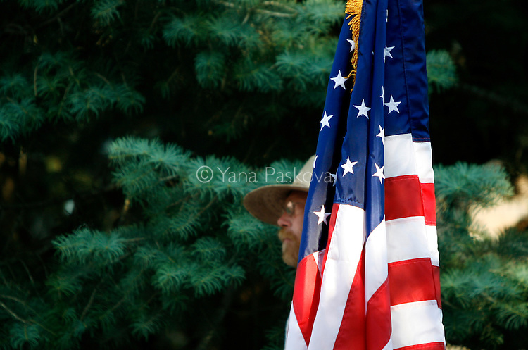 A potential supporter of Democratic Presidential hopeful Hillary Clinton (D-NY) nests by a flag on the roof of a short shed, as the senator and her husband, former President Bill Clinton, prepare their entry to the Iowa State Fairgrounds in Des Moines, Iowa, on July 2, 2007.