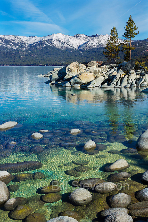 The clear waters of Lake Tahoe at Sand Harbor. In order to accentuate the clarity and color of Lake Tahoe the water must be as smooth as glass. This means not the hint of a puff of a whisper of a breeze. Morning  in the spring time can be good for this.