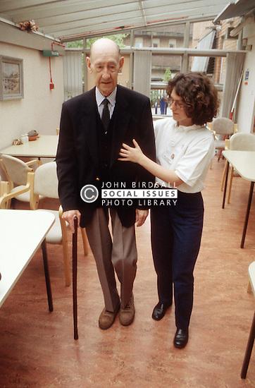 Nursing assistant helping elderly man to walk using a walking stick,