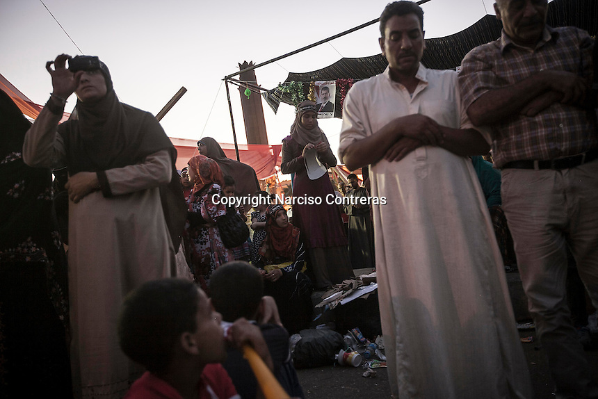 In this Thursday, Aug. 08, 2013 photo, supporters of the ousted president Mohammed Morsi pray at the dusk in the sit-in of the Cairo University at Giza district. (Photo/Narciso Contreras).